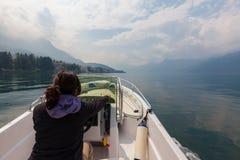 Barco de motor de pilotagem da mulher em um liso, calmo, bonito imagem de stock