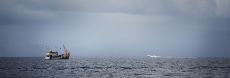 Barco de motor en el horizonte fotos de archivo