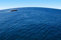 Barco de motor en el planeta azul Imagen de archivo libre de regalías