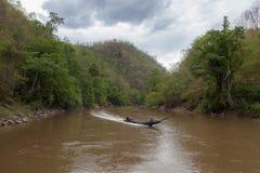 Barco de motor en un río nublado que fluye entre Fotos de archivo