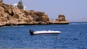 Barco de motor na ?ncora no mar contra a paisagem da praia rochosa e do litoral em Egito filme