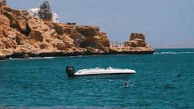 Barco de motor na ?ncora no mar contra a paisagem da praia rochosa e do litoral em Egito video estoque