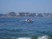 Barco de motor usado para pescar y las excursiones turísticas del Océano Pacífico en ACAPULCO en MÉXICO, paisaje de la bahía foto de archivo