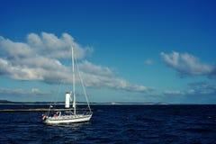 Barco de navegaci?n blanco en curso usando el motor en la tierra del fondo foto de archivo