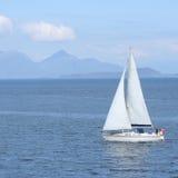 Barco de navegación con la isla Foto de archivo