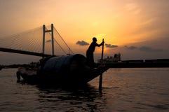 Barco de navegación del hombre en la puesta del sol Fotos de archivo