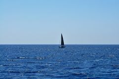 Barco de navegación en el medio del mar Fotos de archivo