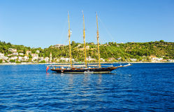 Barco de navegación en el ront de la orilla de mar y del cielo azul Imagenes de archivo