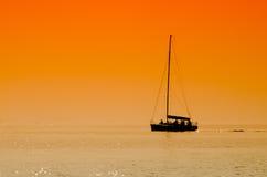 Barco de navegación en puesta del sol Foto de archivo libre de regalías