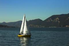 Barco de navegación en un lago rodeado con las montañas foto de archivo libre de regalías