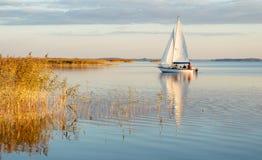 Barco de navegación en un lago tranquilo con la reflexión fotografía de archivo