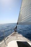 Barco de navegación que cruza en el mar Foto de archivo