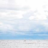 Barco de navegación solo en el mar, el cielo nublado y el agua de la plata Fotos de archivo libres de regalías