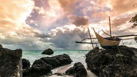 Barco de navegación viejo en la puesta del sol en la isla tropical superior de Boracay de las rocas, Filipinas 4K TimeLapse - ago