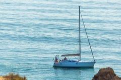 Barco de navigação ancorado perto da costa e das rochas Lagos, Portugal fotos de stock royalty free