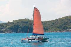 Barco de navigação bonito com uma vela vermelha no mar perto da praia Mar azul no tempo ensolarado fotografia de stock royalty free