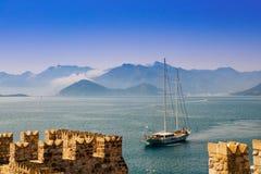 Barco de navigação no nascer do sol no mar pelo castelo histórico Imagens de Stock Royalty Free