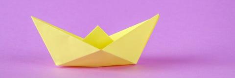 Barco de papel amarelo do origâmi com uma folha do outono em um fundo roxo imagem de stock royalty free