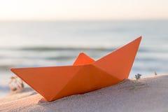 Barco de papel anaranjado en una playa Imagenes de archivo