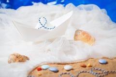 Barco de papel com areia, cordas, água imagem de stock royalty free