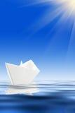 Barco de papel e água azul fotos de stock royalty free