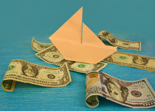 Barco de papel en las ondas en el mar del dinero Imágenes de archivo libres de regalías