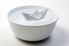 Barco de papel en tazón de fuente por completo de agua Foto de archivo libre de regalías