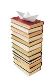 Barco de papel en una pila de libros imagenes de archivo