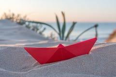 Barco de papel rojo en una playa Imágenes de archivo libres de regalías