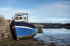 Barco de pesca abandonado en el muelle durante la bajamar Fotografía de archivo