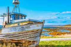 Barco de pesca abandonado velho brilhante na costa foto de stock royalty free