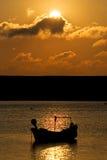 Barco de pesca amarrado en el mar durante puesta del sol fotografía de archivo