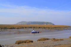 Barco de pesca amarrado en el río durante la bajamar imagenes de archivo