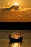 Barco de pesca amarrado no mar durante o por do sol Fotografia de Stock