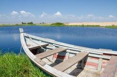 Barco de pesca anclado en laguna con la hierba verde y las dunas Foto de archivo libre de regalías