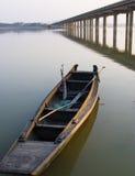 Barco de pesca bajo un puente Foto de archivo libre de regalías
