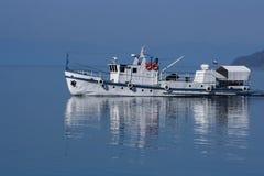 Barco de pesca blanco en el lago Baikal, Rusia en madrugada Fotografía de archivo