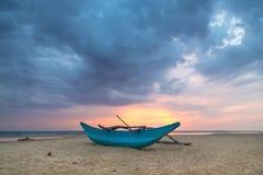 Barco de pesca cingalês tradicional no Sandy Beach no por do sol. imagens de stock