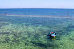 Barco de pesca colorido en el mar cristalino con la parte inferior arenosa visible y el horizonte claro Fotos de archivo
