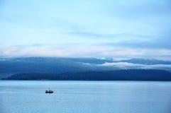 Barco de pesca com montanhas e as baixas nuvens imagem de stock