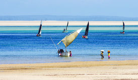 Barco de pesca com trabalhadores e maré baixa Imagens de Stock Royalty Free