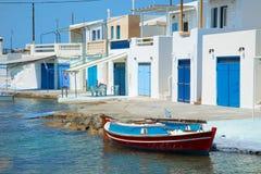 Barco de pesca com uma vila no fundo fotos de stock