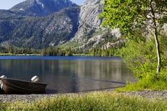 Barco de pesca de aluminio en la orilla del lago mountain Imágenes de archivo libres de regalías