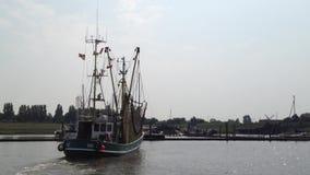 Barco de pesca/barco del camarón que deja el puerto en Greetsiel, Frisia del este Ostfriesland, Alemania metrajes