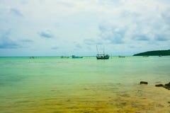 Barco de pesca del pescador en el océano de la agua de mar verde debajo del cielo nublado azul fotos de archivo