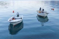 Barco de pesca dois branco pequeno na água calma Foto de Stock