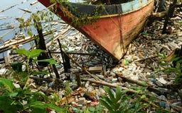 Barco de pesca e lotes abandonados do desperdício do plástico imagem de stock royalty free