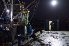 Barco de pesca en el área de embarque en la noche que se prepara para ir al mar con los hombres y los funcionarios del barco rast foto de archivo