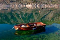 Barco de pesca en el agua clara, la ciudad vieja y montañas en el fondo foto de archivo