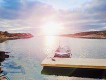 Barco de pesca en el agua de la calma de la puesta del sol Una motora para la pesca deportiva atada a un embarcadero de madera Foto de archivo libre de regalías